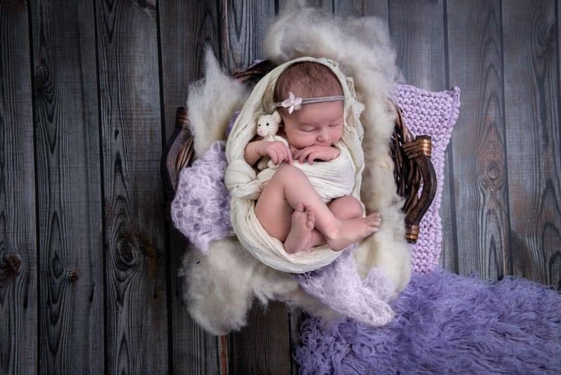 Baby in Korb mit Teddy