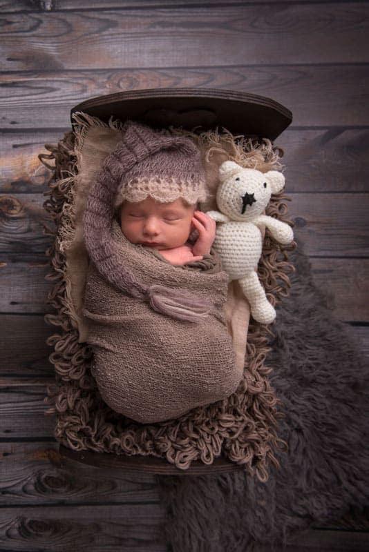 Newbornphotography Baby im Bett mit Teddy